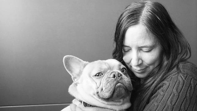 woman cuddling french bulldog - black & white image